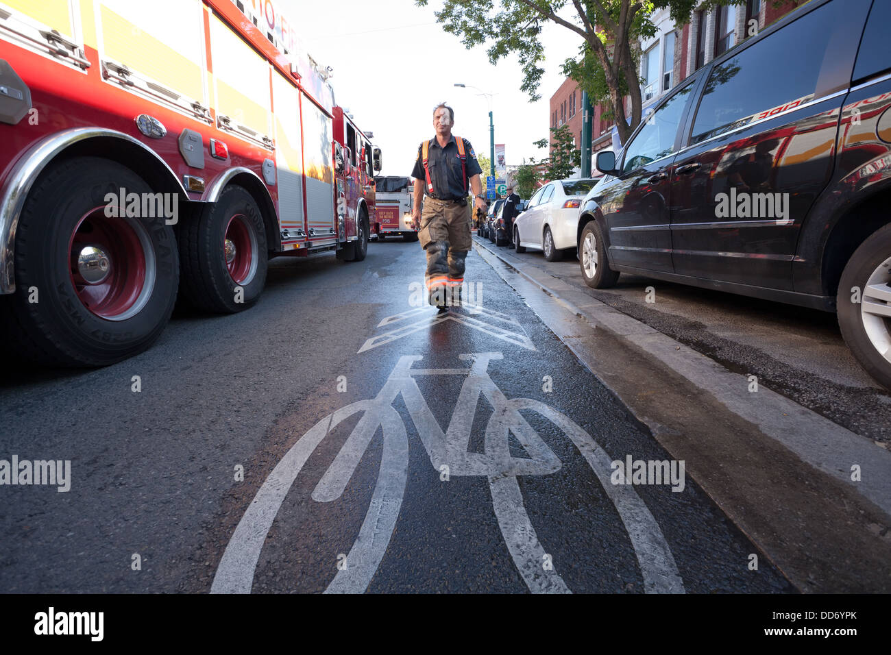 A firefighter walking towards a bike lane marking during a fire in Kensington Market, Toronto, Ontario, Canada. - Stock Image