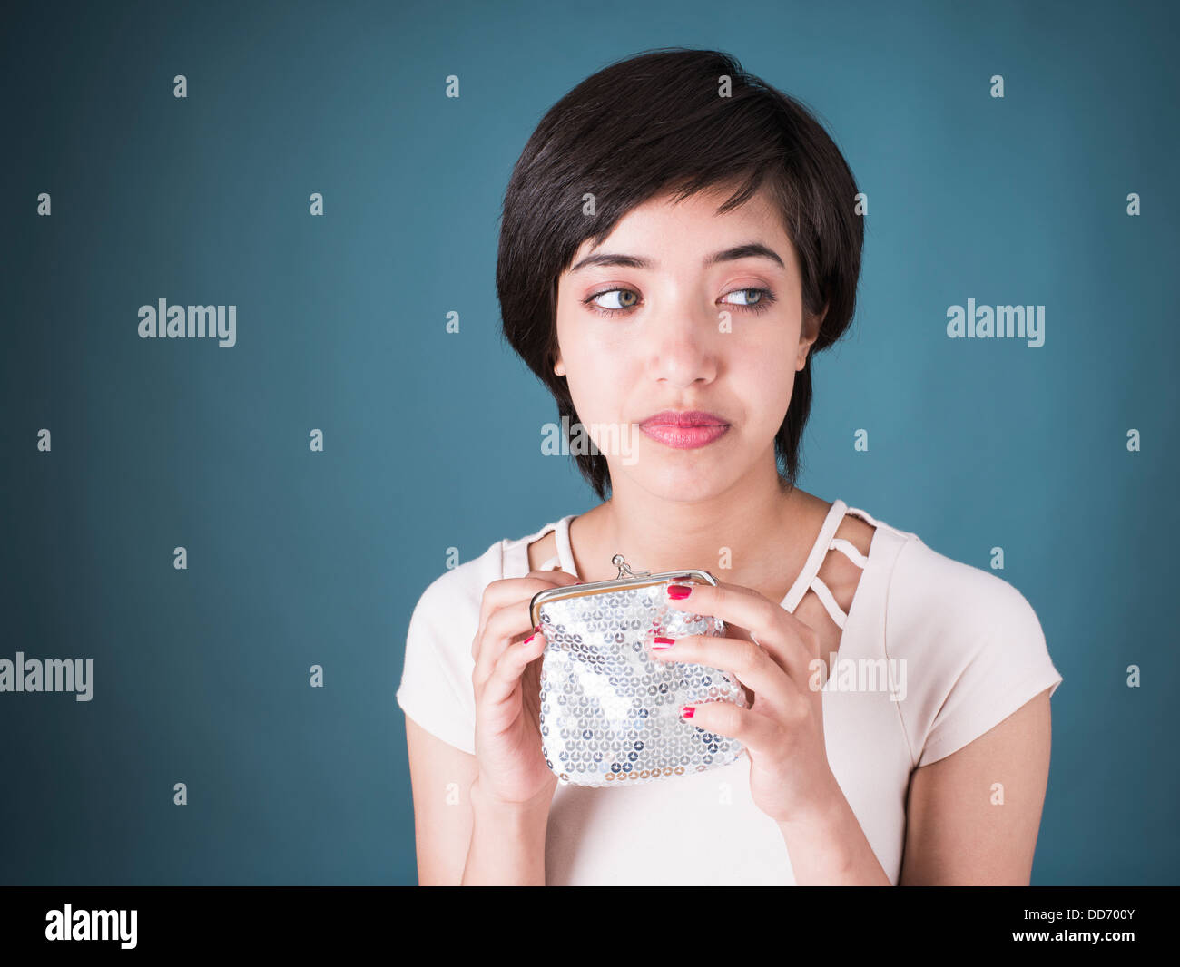 Portrait of sad young multiracial woman looking in empty silver wallet - Stock Image