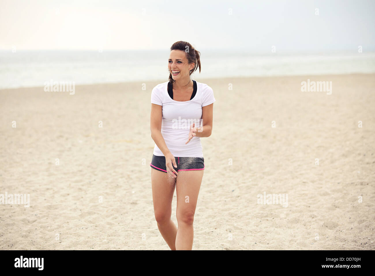 Attractive cheerful woman at the summer beach having fun. Candid shot of beautiful happy model smiling. - Stock Image