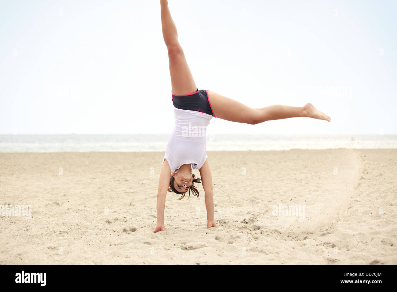 Happy outdoor female doing cartwheel on the beach. Healthy and active lifestyle shot expressing happiness and joy. - Stock Image