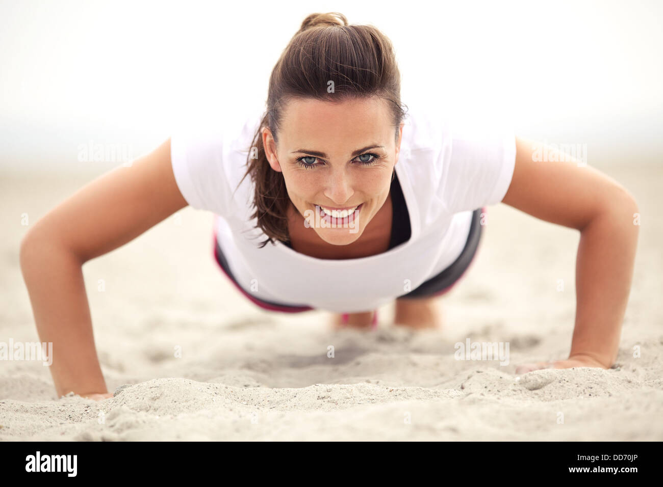 Happy fitness caucasian woman on the beach smiling while doing push up exercise. Active and healthy lifestyle. - Stock Image