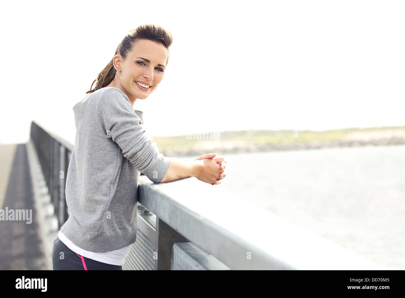 Happy smiling woman in fitness wear resting after running workout. Looking relaxed at camera. Copy space right. - Stock Image