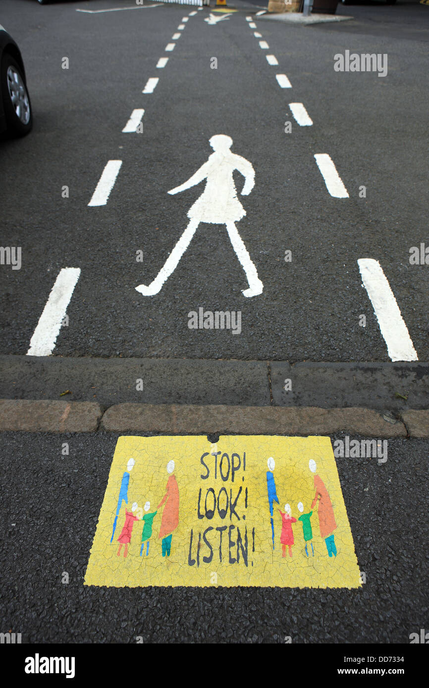Stop Look and Listen sign, aimed at children, on the pavement in the Scottish village of Aberdour in Fife Scotland - Stock Image