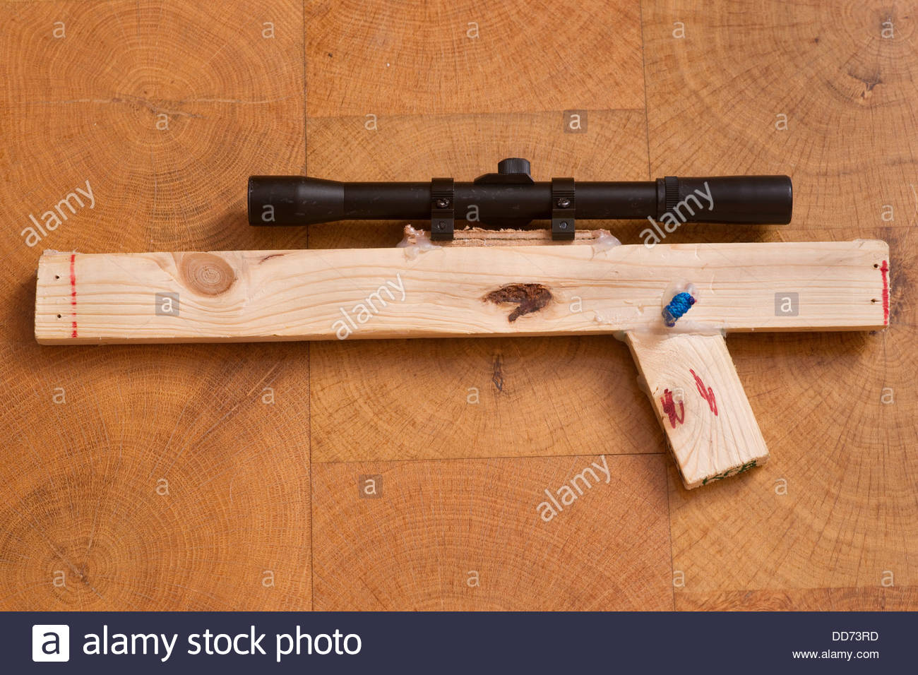 boy child children kid kids playing with toy gun wooden wood homemade with real sniper scope - Stock Image
