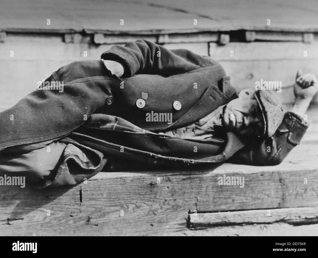 Man sleeping on the NYC docks, ca. 1930-31, by Lewis Hine. He wears a three piece suit under his worn overcoat, - Stock Image