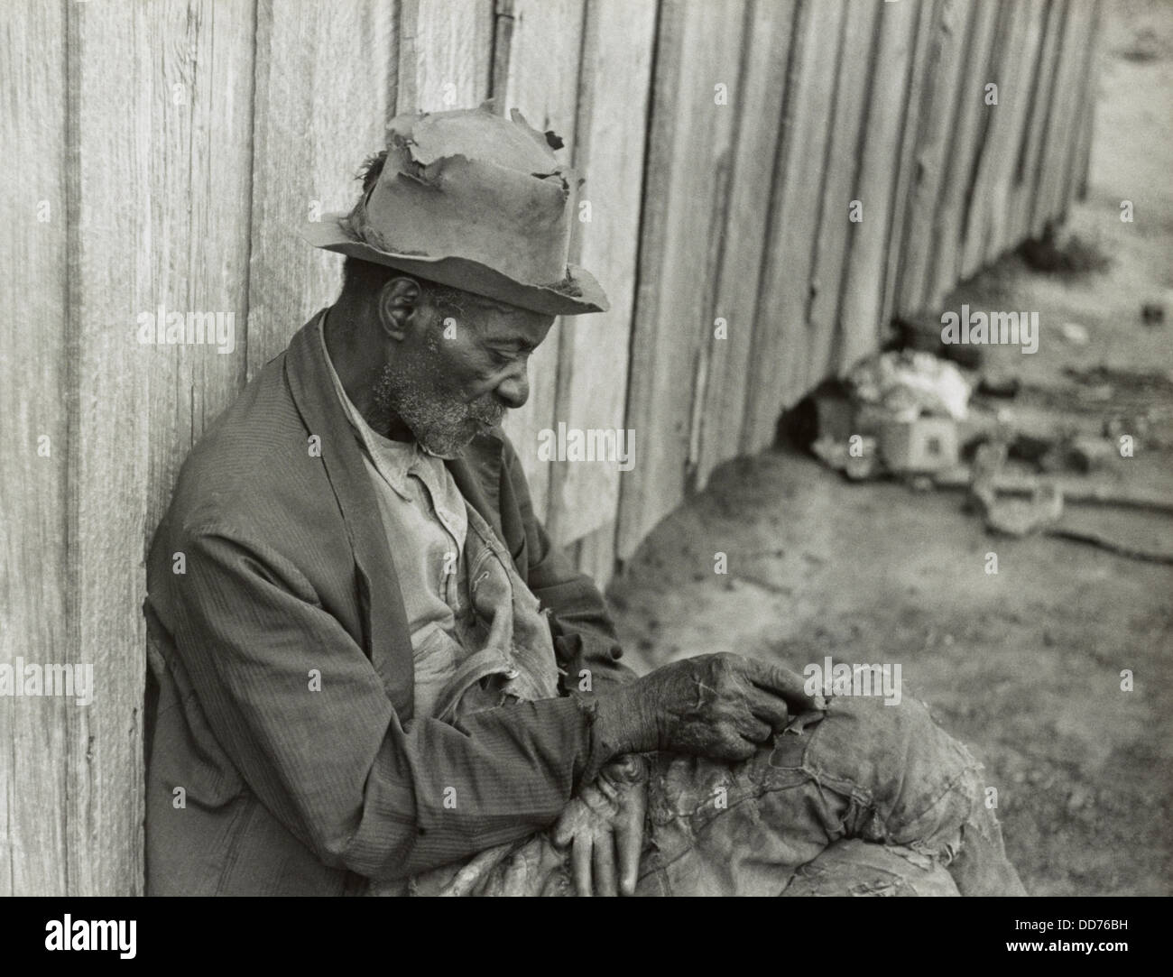 african american man with missing fingers wearing tattered clothing