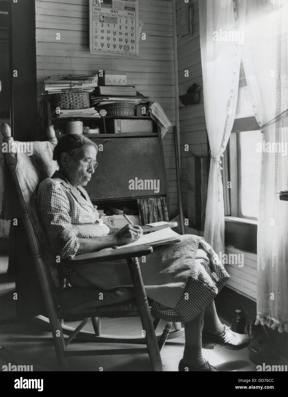 Elderly African American Woman Writing In A Rocking Chair