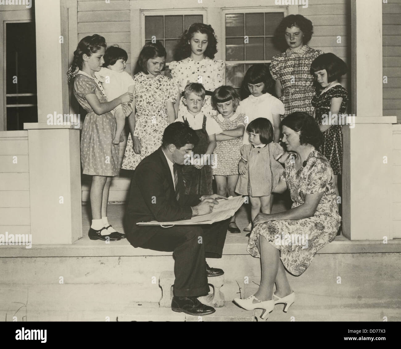 1940 Census taker interviewing the mother of ten children. On their front porch, the family is well dressed and - Stock Image