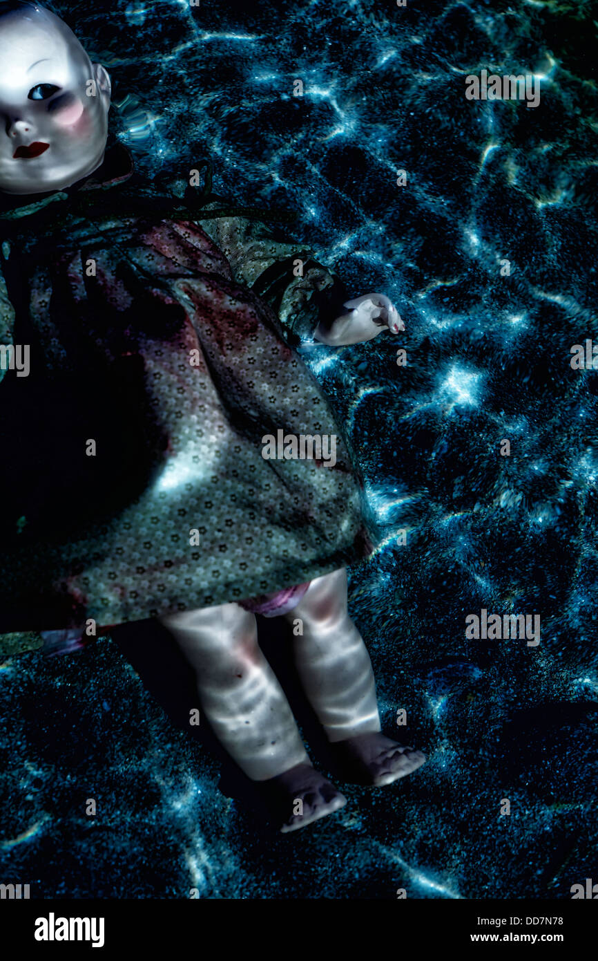 a doll floating in water in moonlight - Stock Image