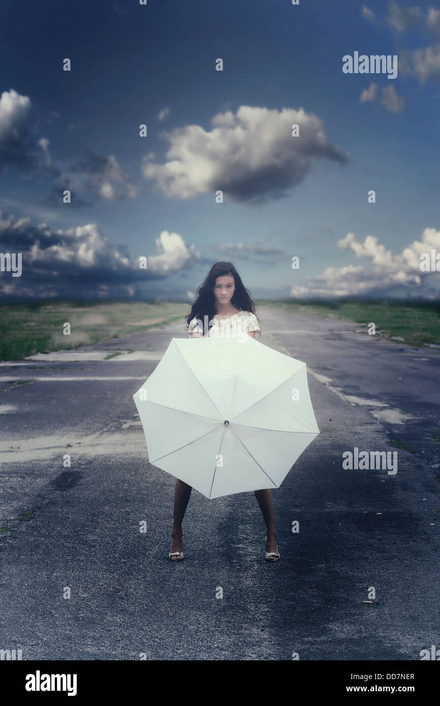 a girl in a floral dress on a street with a white umbrella - Stock Image