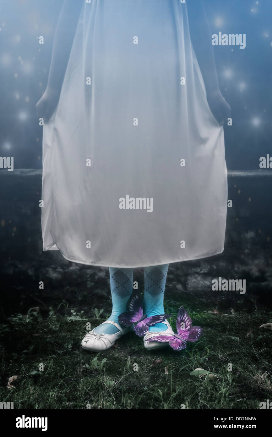 a girl in a white nightdress standing outside at night with two butterflies on her feet - Stock Image