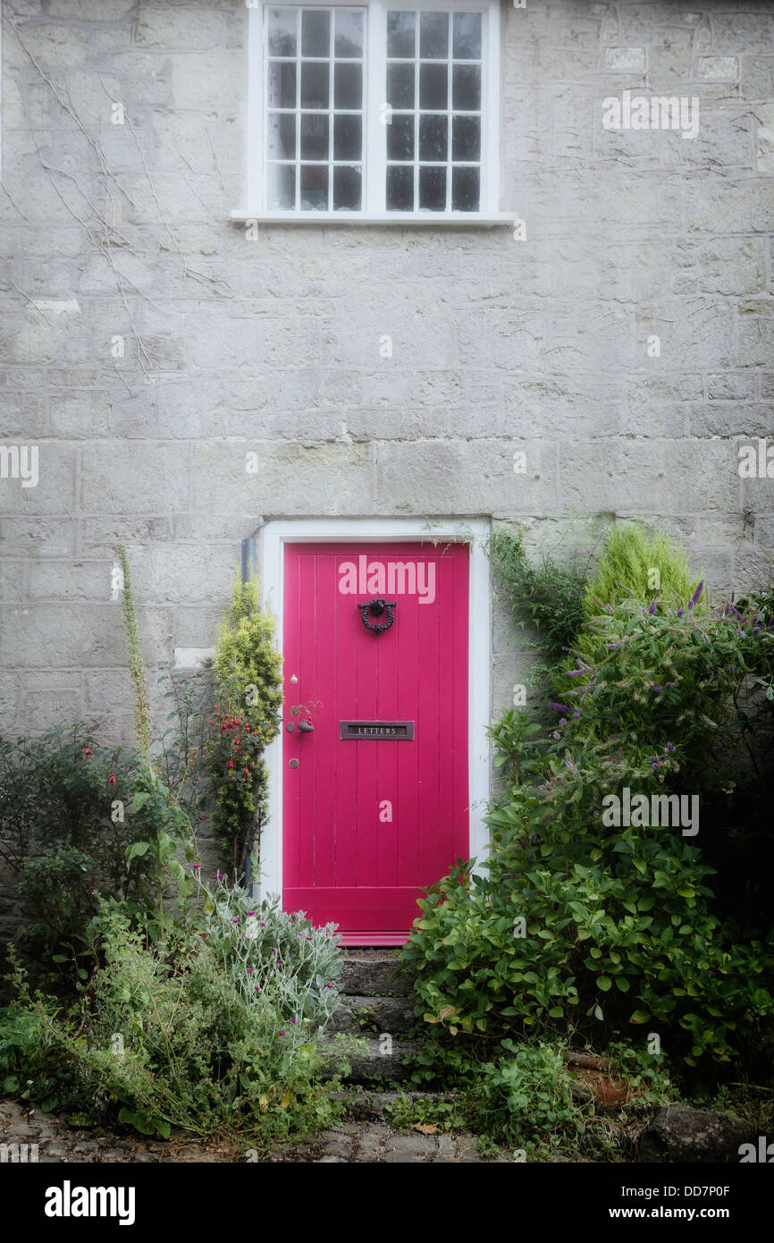 a pink door at an old cottage - Stock Image