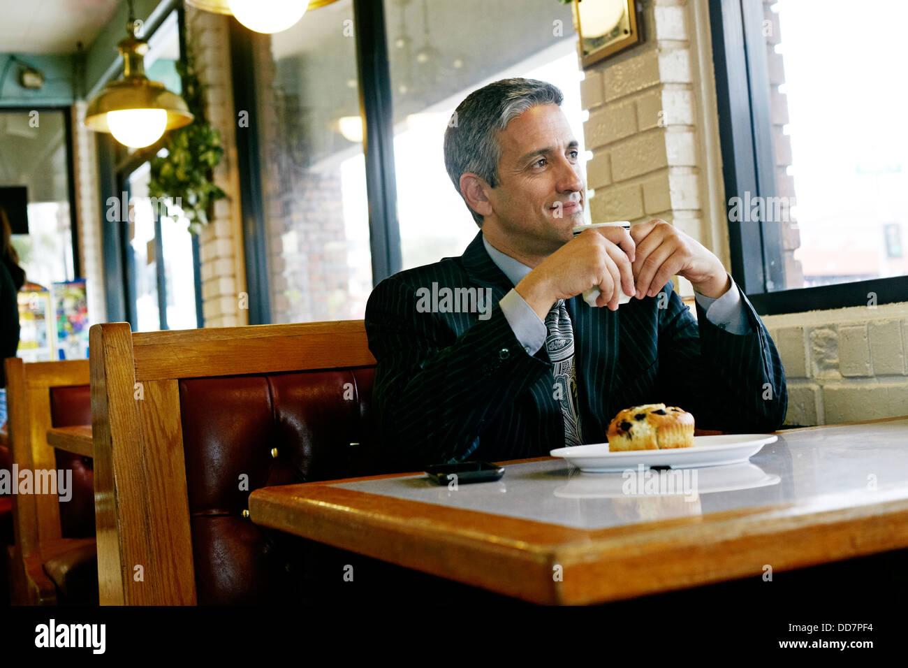 Hispanic businessman having coffee in restaurant Stock Photo