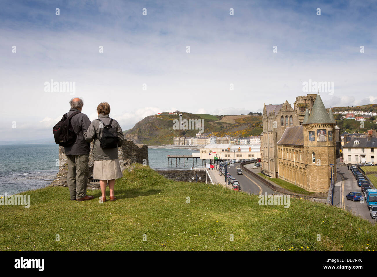 UK, Wales, Ceredigion, Aberystwyth, middle aged couple on Castle mound overlooking first University building - Stock Image