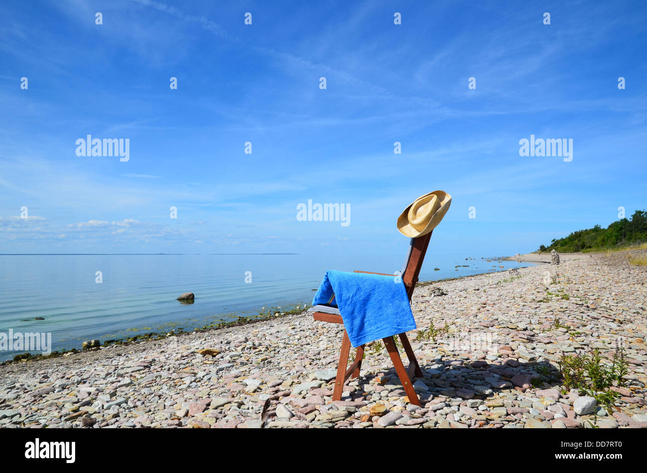 Lone chair with towel and hat at summertime by the coast - Stock Image