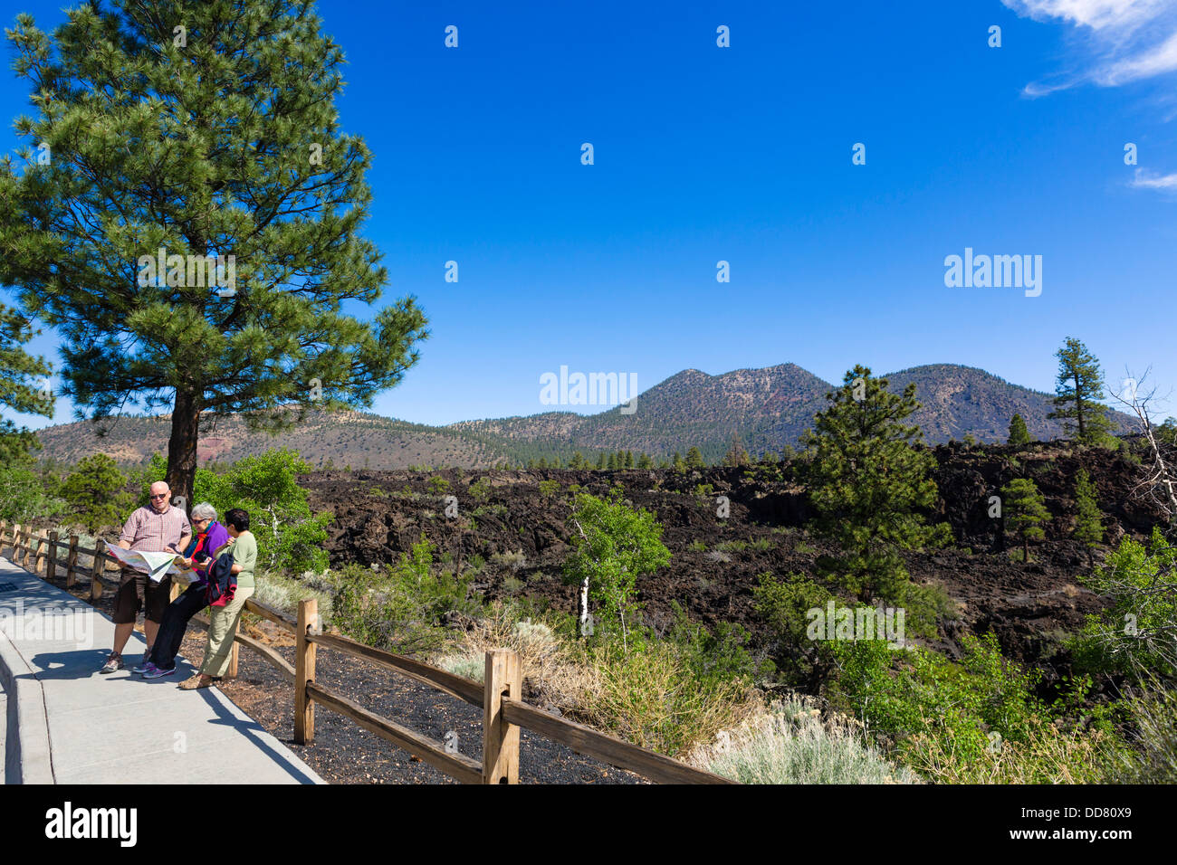 Tourists at a viewpoint overlooking the Bonito Lava Flow, Sunset Crater Volcano National Monument, near Flagstaff, - Stock Image