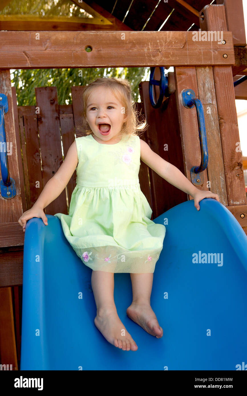 Two years old girl fulfilled on the blue slide that attached to the wooden playground - Stock Image