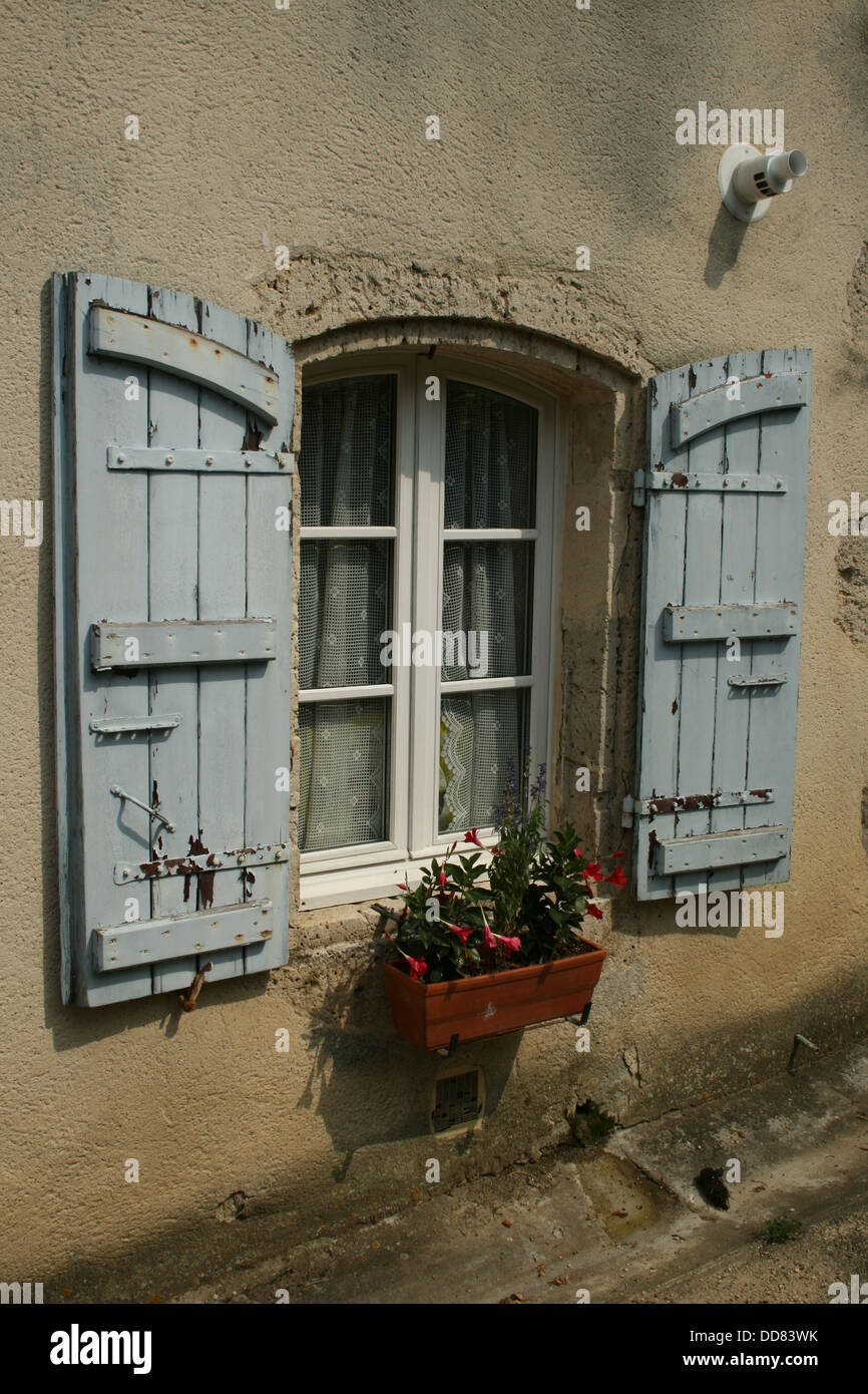 Typical blue French arch window shutters with flowers in window box - Stock Image