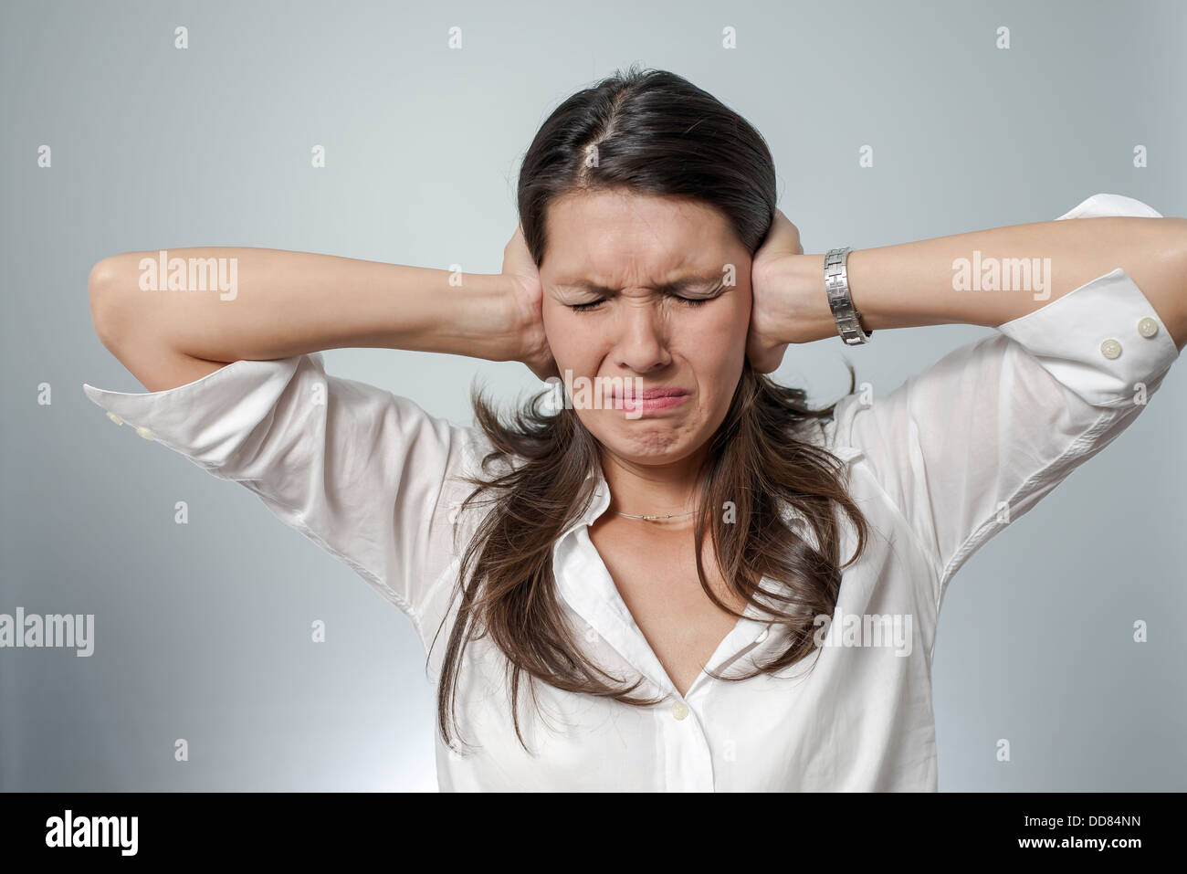 woman with headache and negative face expression - burn-out, depression, frustration, sickness - Stock Image
