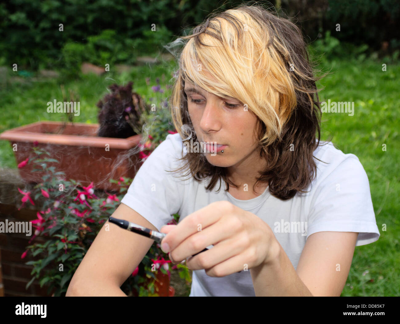 A teenage boy sitting in a garden, smoking an electronic cigarette and exhaling vapour - Stock Image