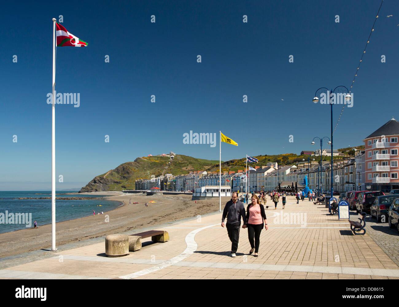 UK, Wales, Ceredigion, Aberystwyth, visitors walking on sunny promenade - Stock Image