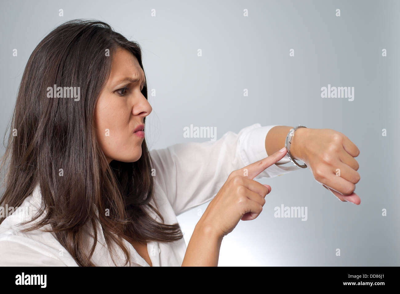 woman watch wrist show tapping late time finger - Stock Image