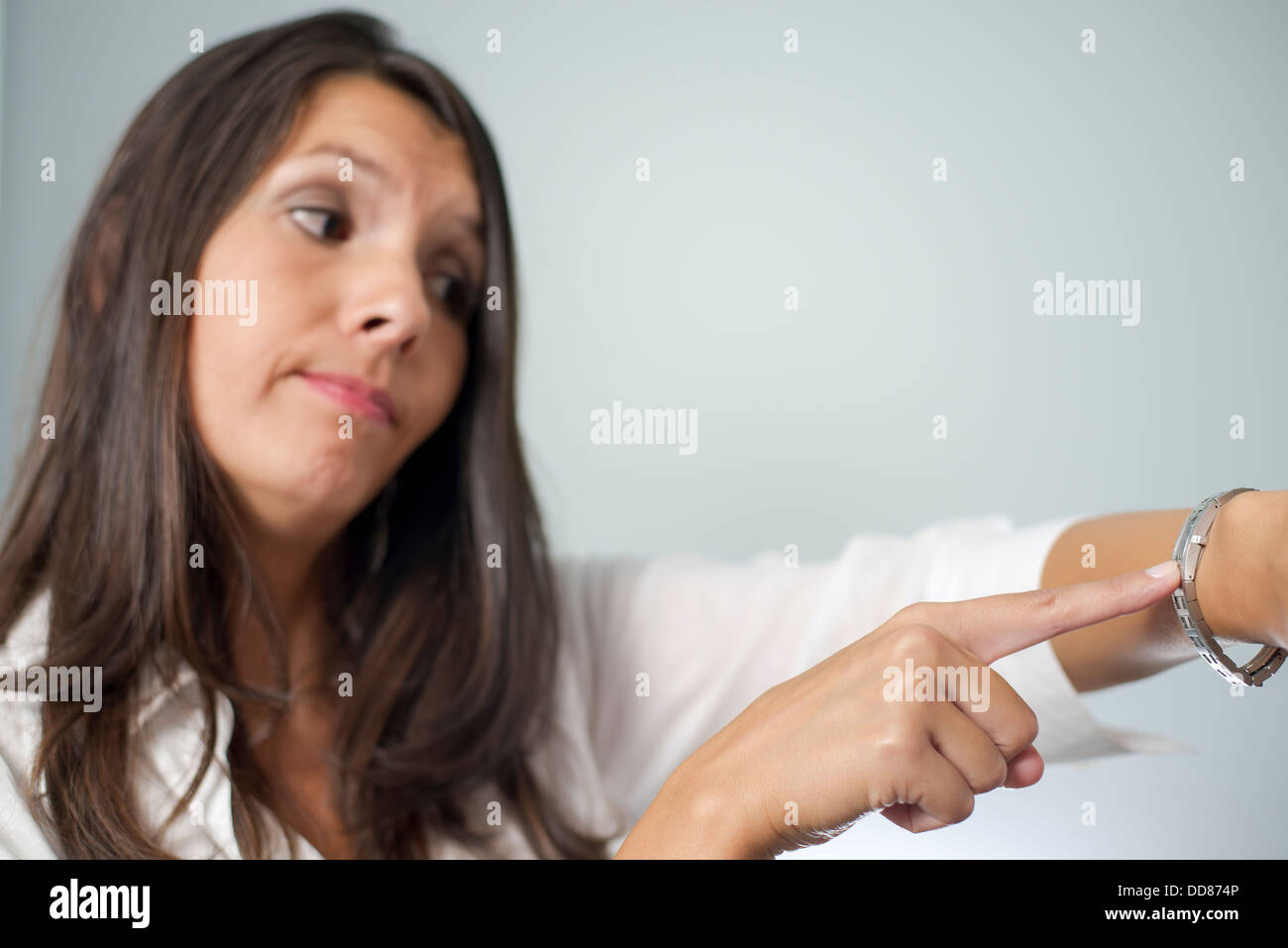 Irritated businesswoman tapping her watch and frowning as she is kept waiting for an appointment by an unpunctual - Stock Image
