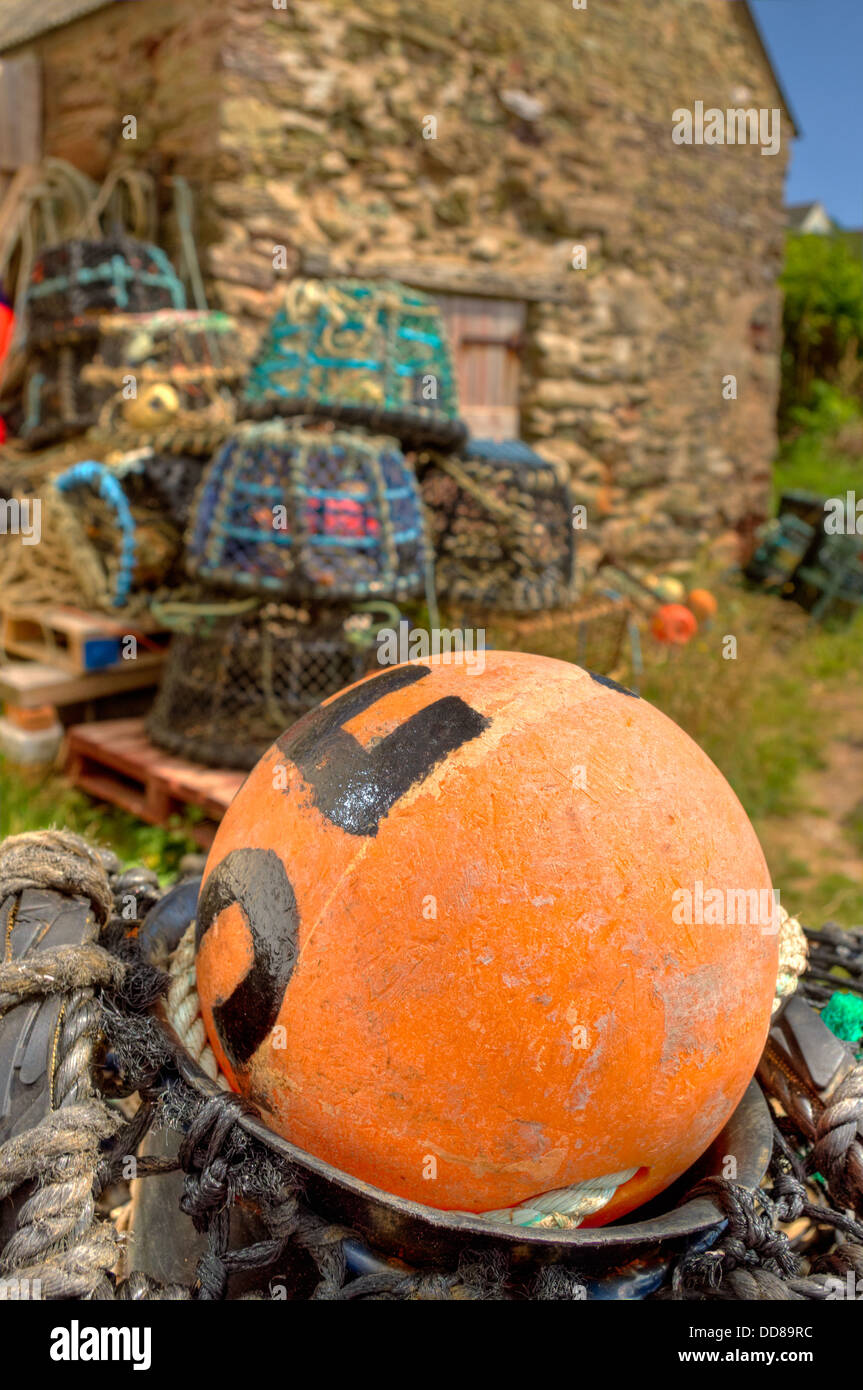 Lobster and crab pots stored above the harbour wall at Inner Hope Cove in the 'South Devon Area of Outstanding Natural Stock Photo