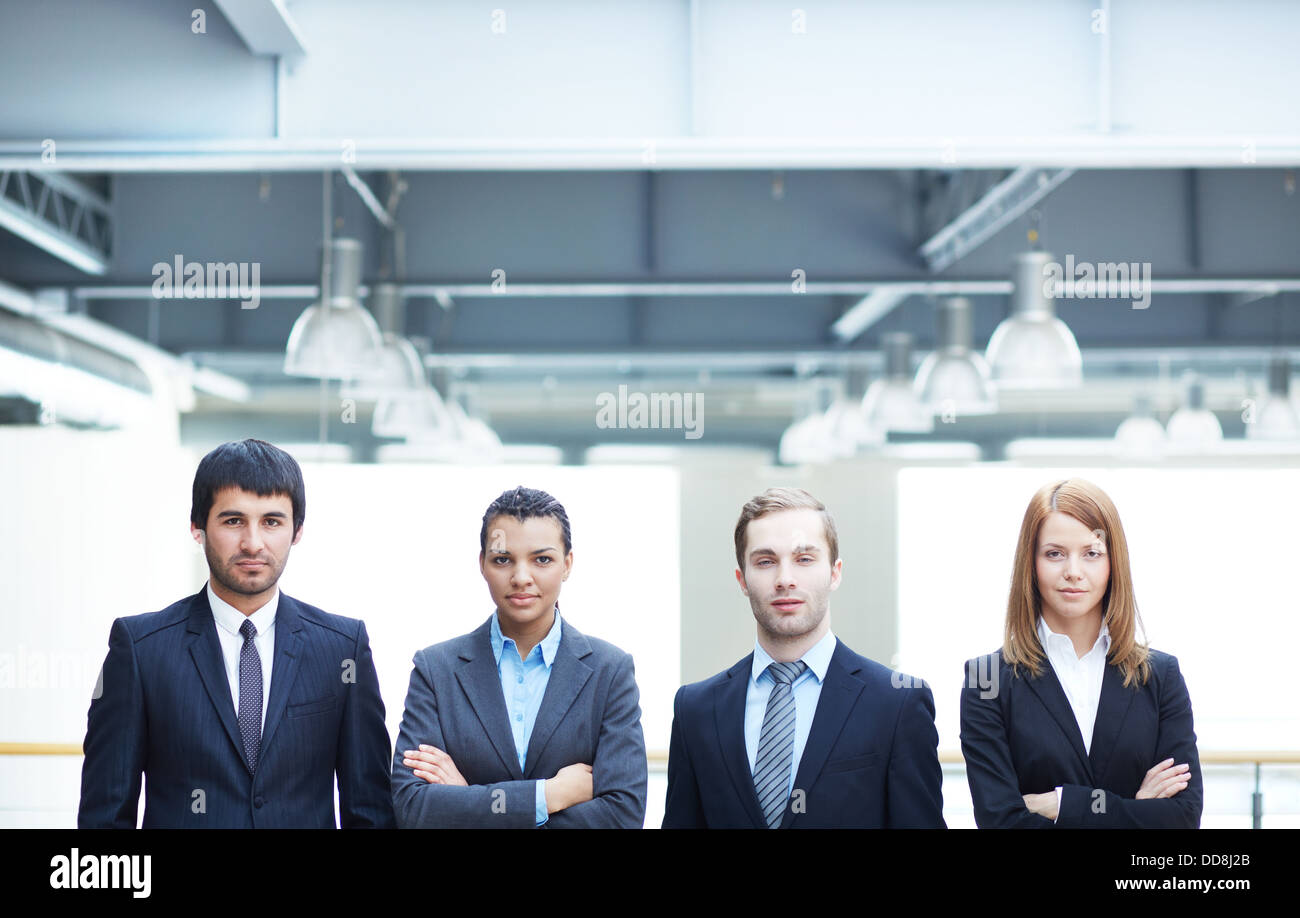 Group of confident businesspeople in suits standing in line - Stock Image