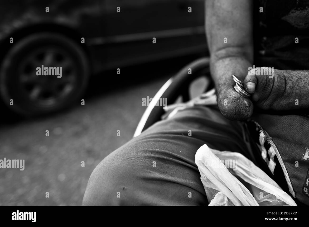 A Colombian disabled athlete counts money earned by selling pocket calendars on the motorway in Bogota, Colombia. - Stock Image