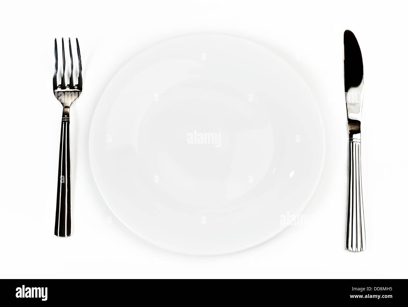 Plate with silverware: knife and fork, over white - Stock Image