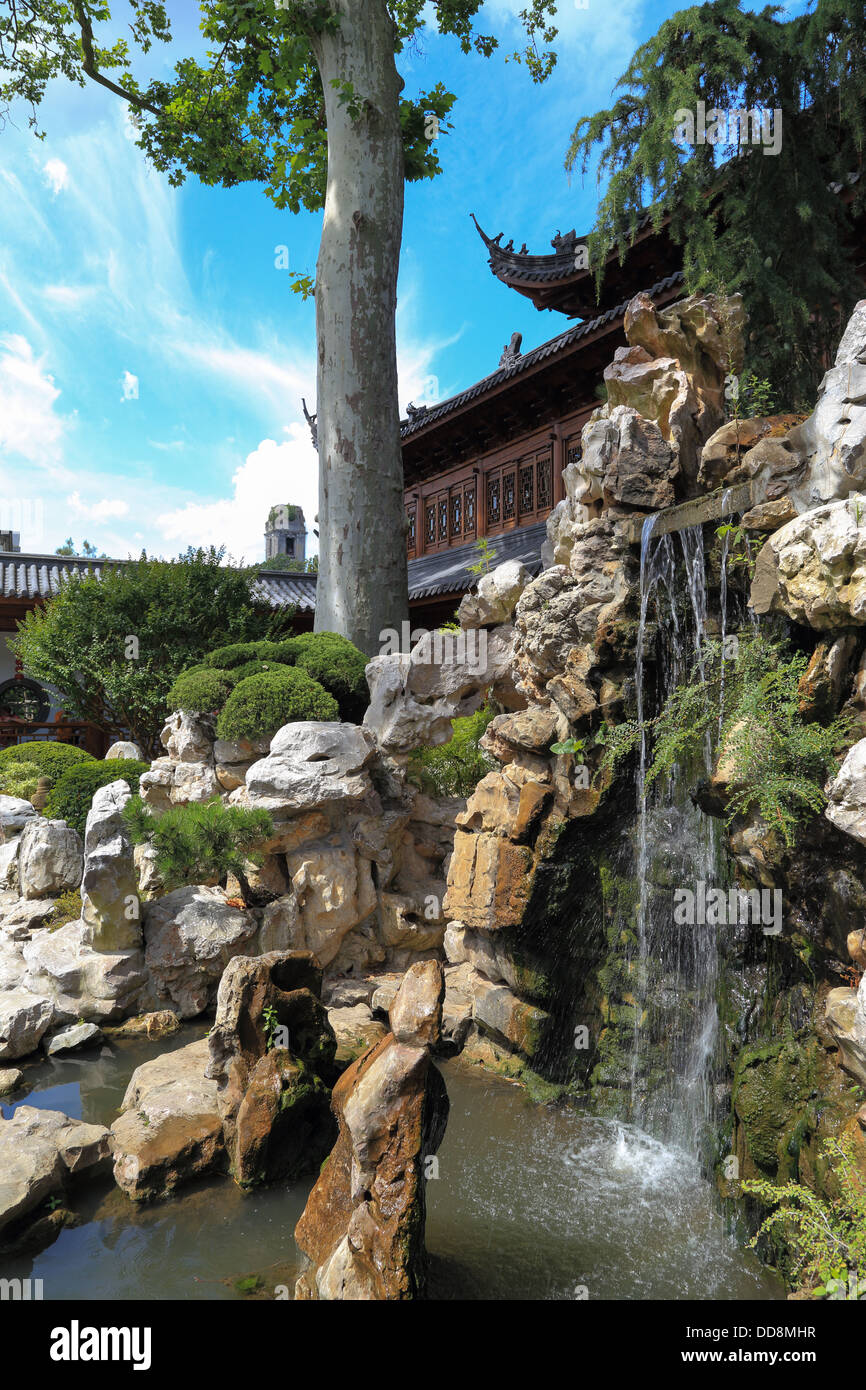 Chinese Temple In A Nice Garden With A Waterfall Trees And Stones