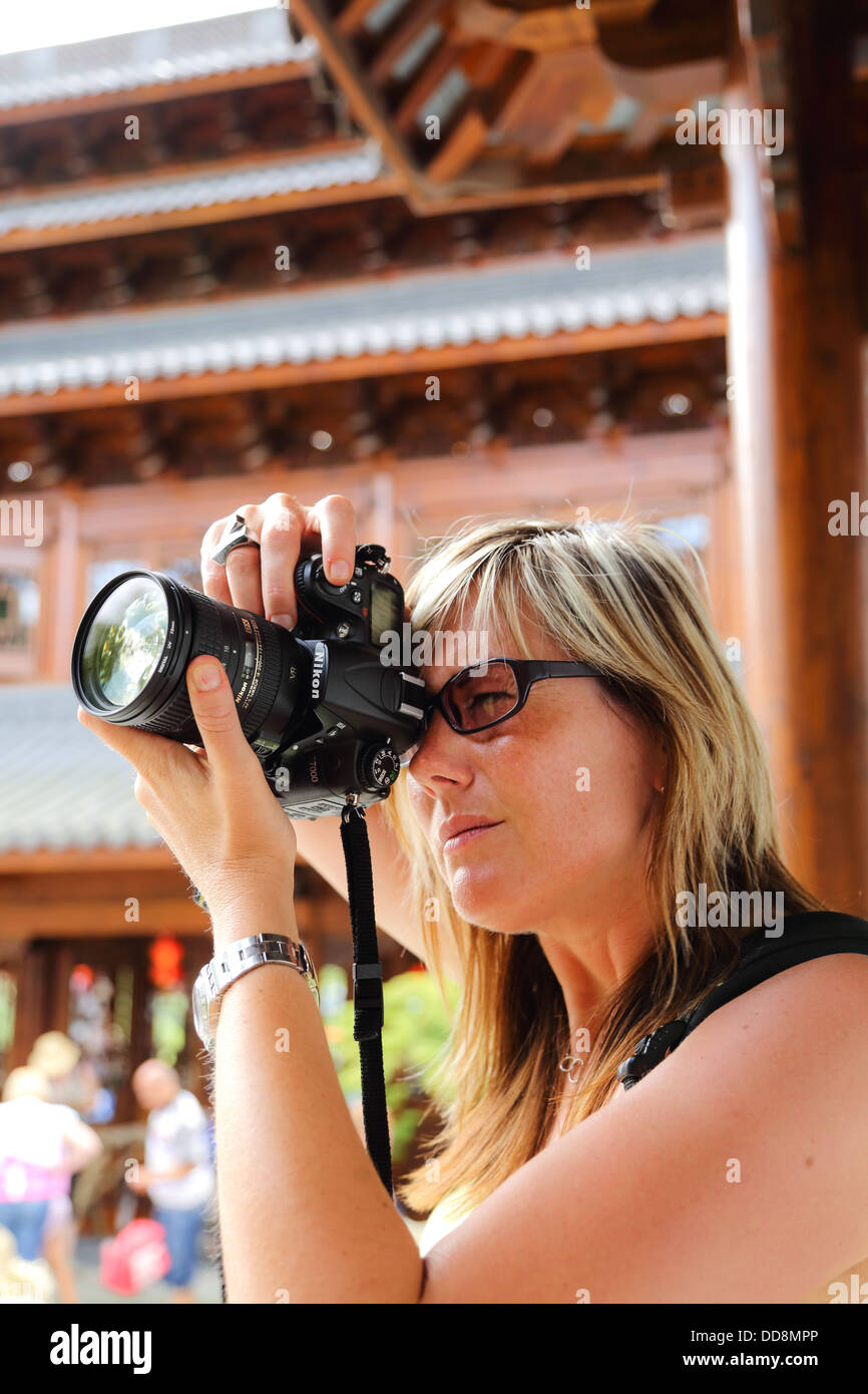 European white woman, blond hair, taking a photo in a chinese temple with a digital SLR camera. Focused on the woman - Stock Image