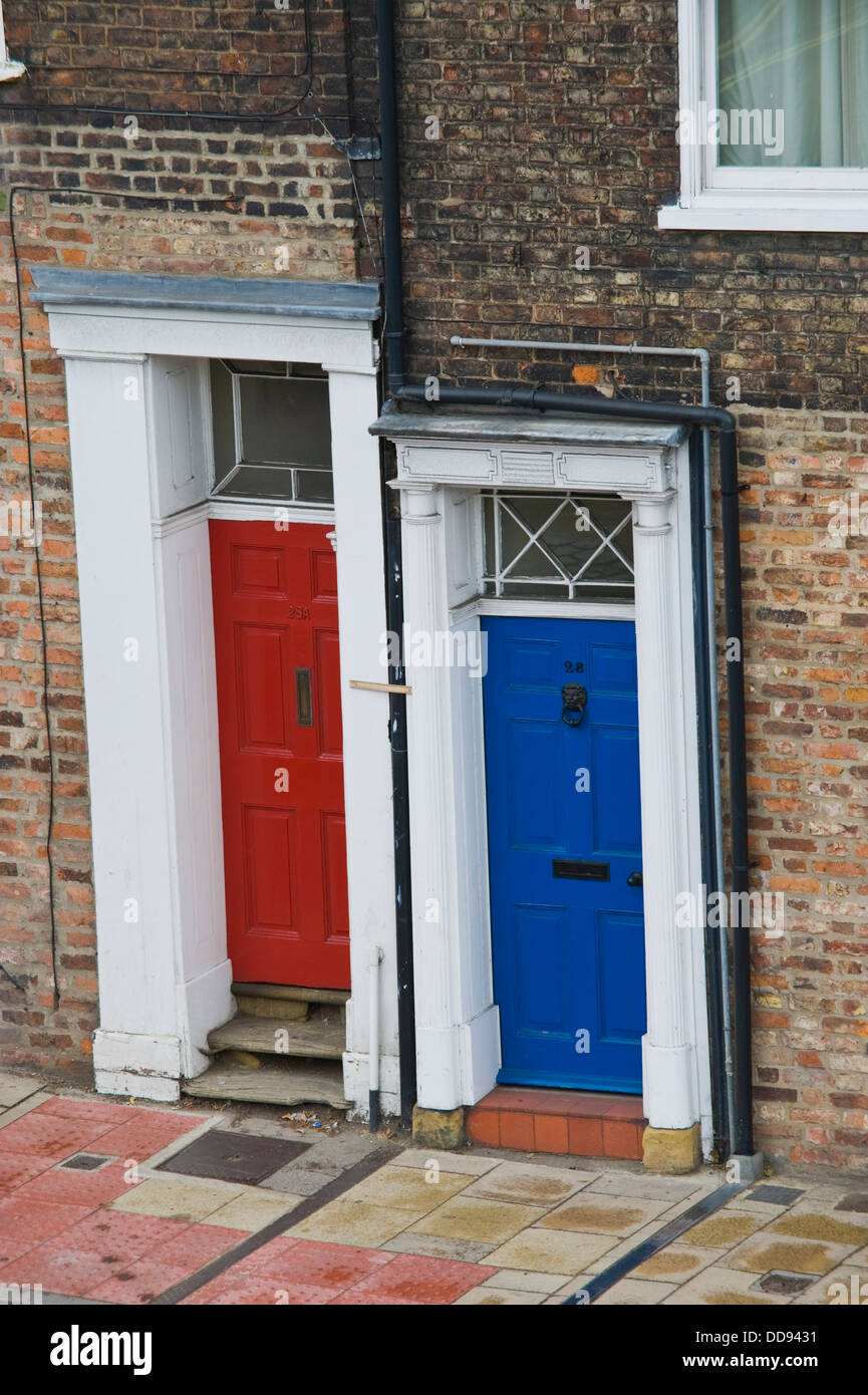 Red and blue front doors of terraced houses in city of York North ...