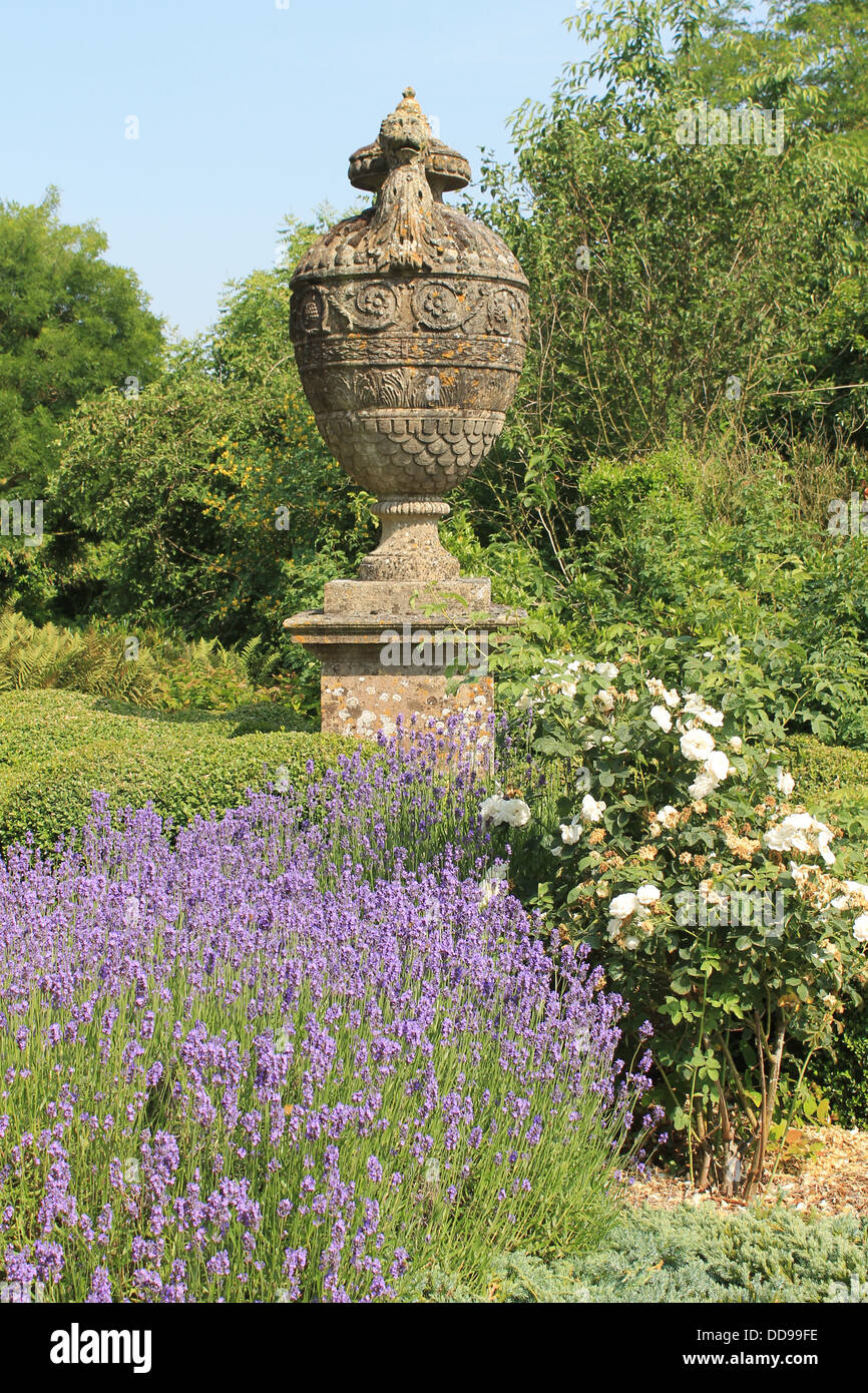 Enormous stone urn with lavender and white roses in the garden of Petworth House, West Sussex, UK - Stock Image