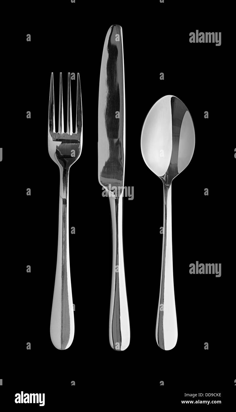 Silver cutlery set against a black background great concept for food festivals or fine dining competitions - Stock Image
