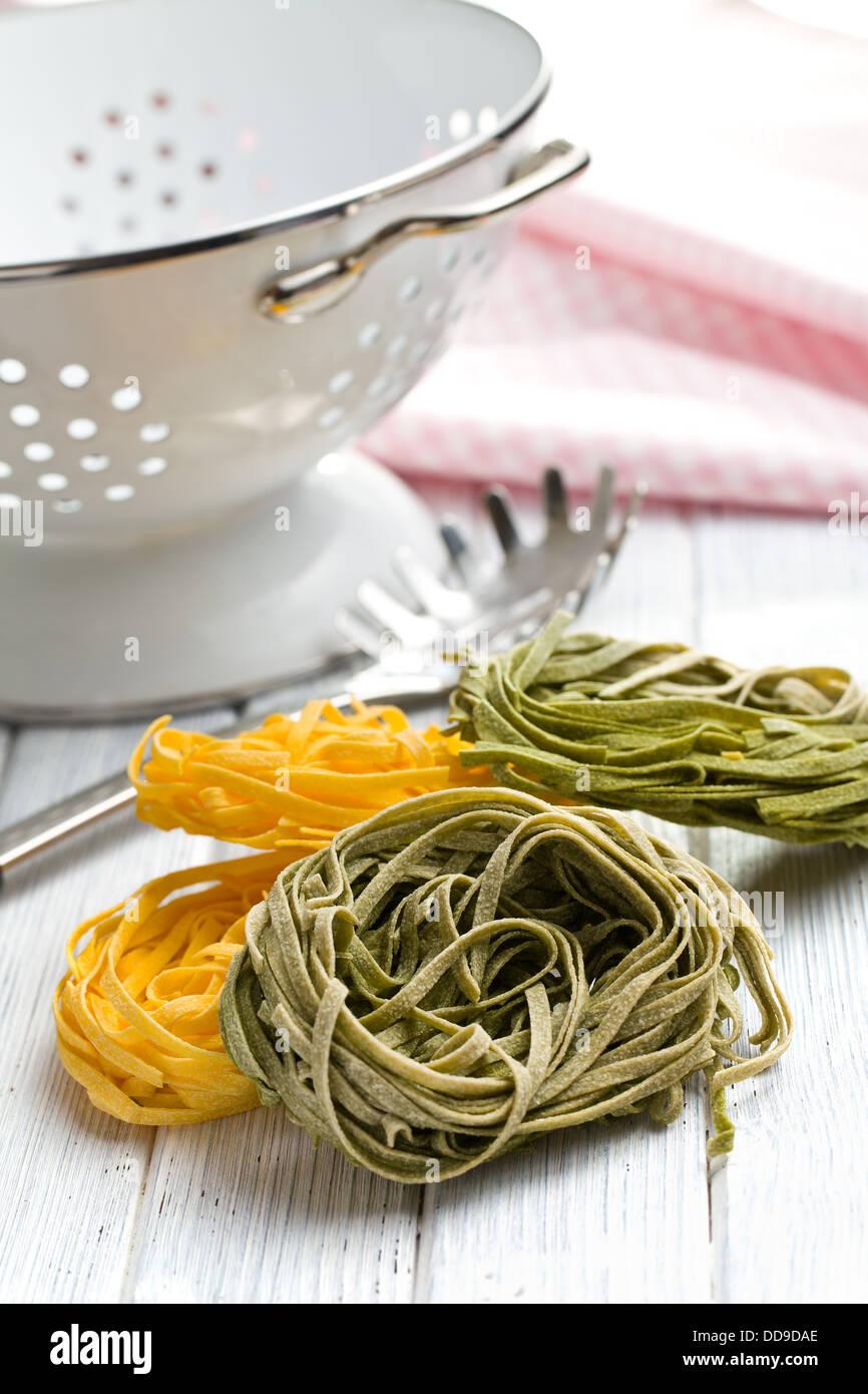Italian pasta tagliatelle on wooden table - Stock Image
