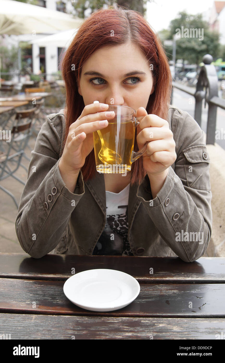 young woman drinking tea in an outdoor cafe - Stock Image