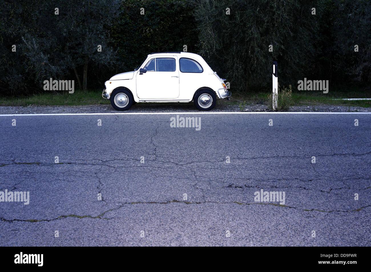 Old italian car 500 FIAT on a desert road - Stock Image