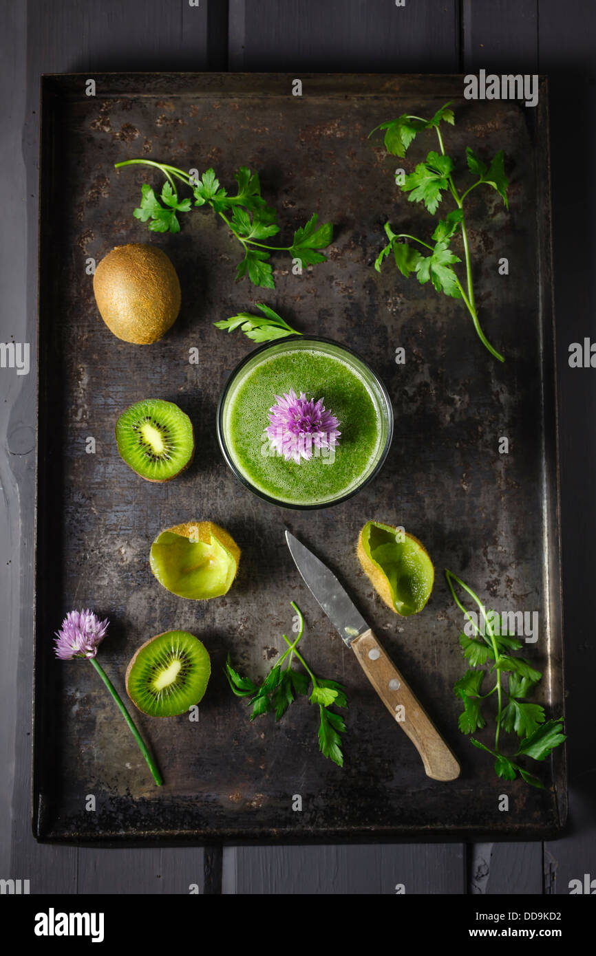 Glass of smoothie with kiwi, parsley and blooming chives, close up - Stock Image