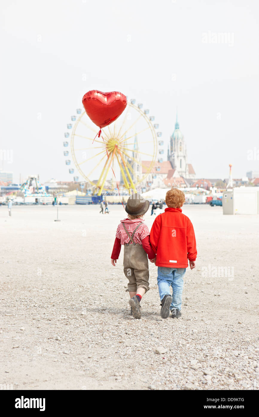 Germany, Bavaria, Munich, boys with heart shaped balloon going to Oktoberfest - Stock Image