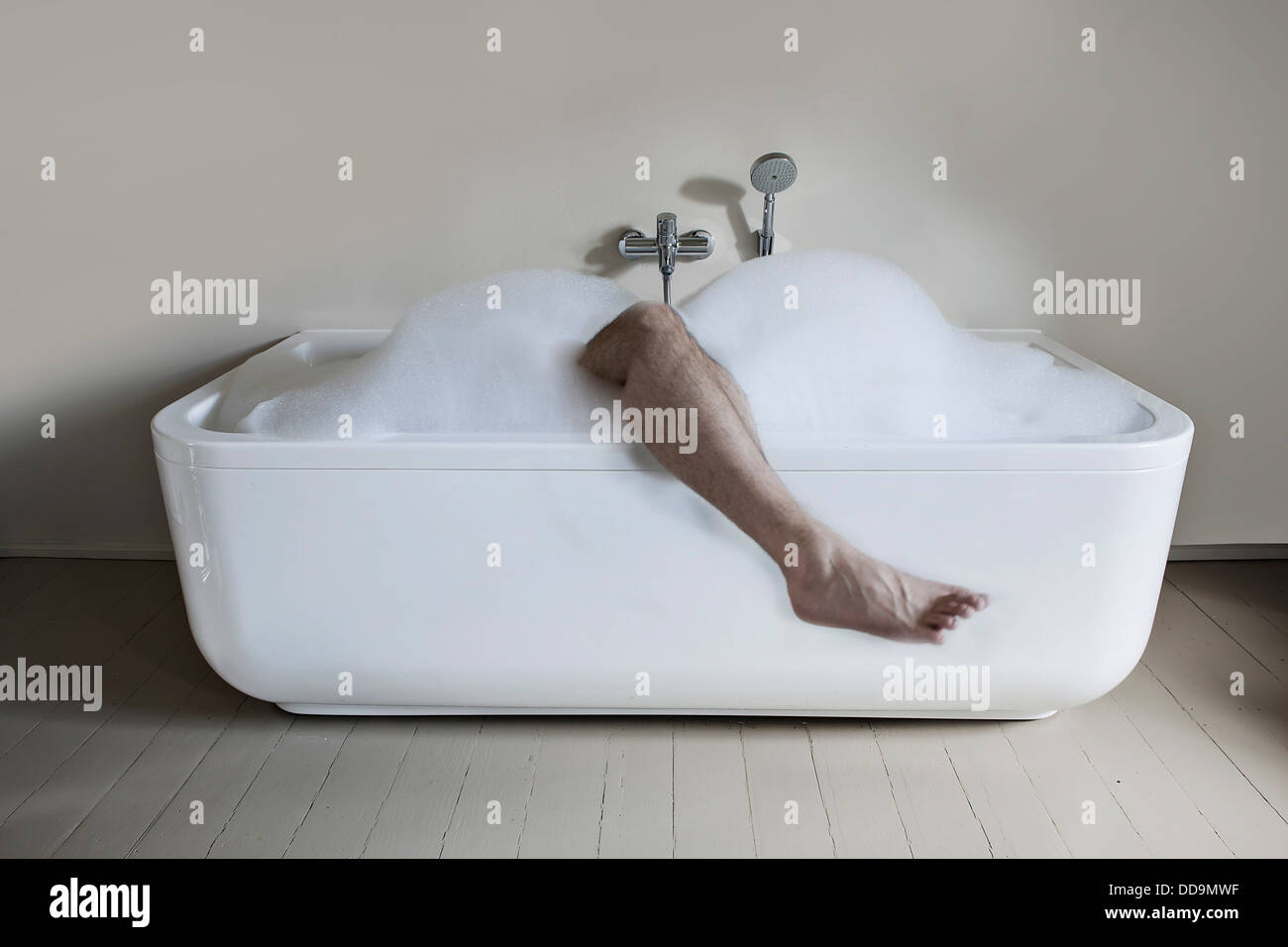 Mid adult man in bathtub with leg out - Stock Image