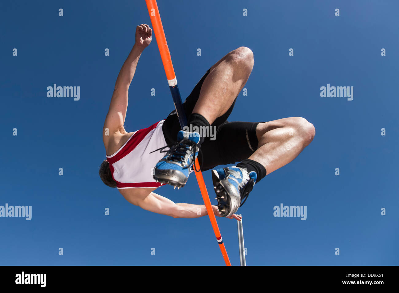 Germany, Mature man curling over high jump - Stock Image