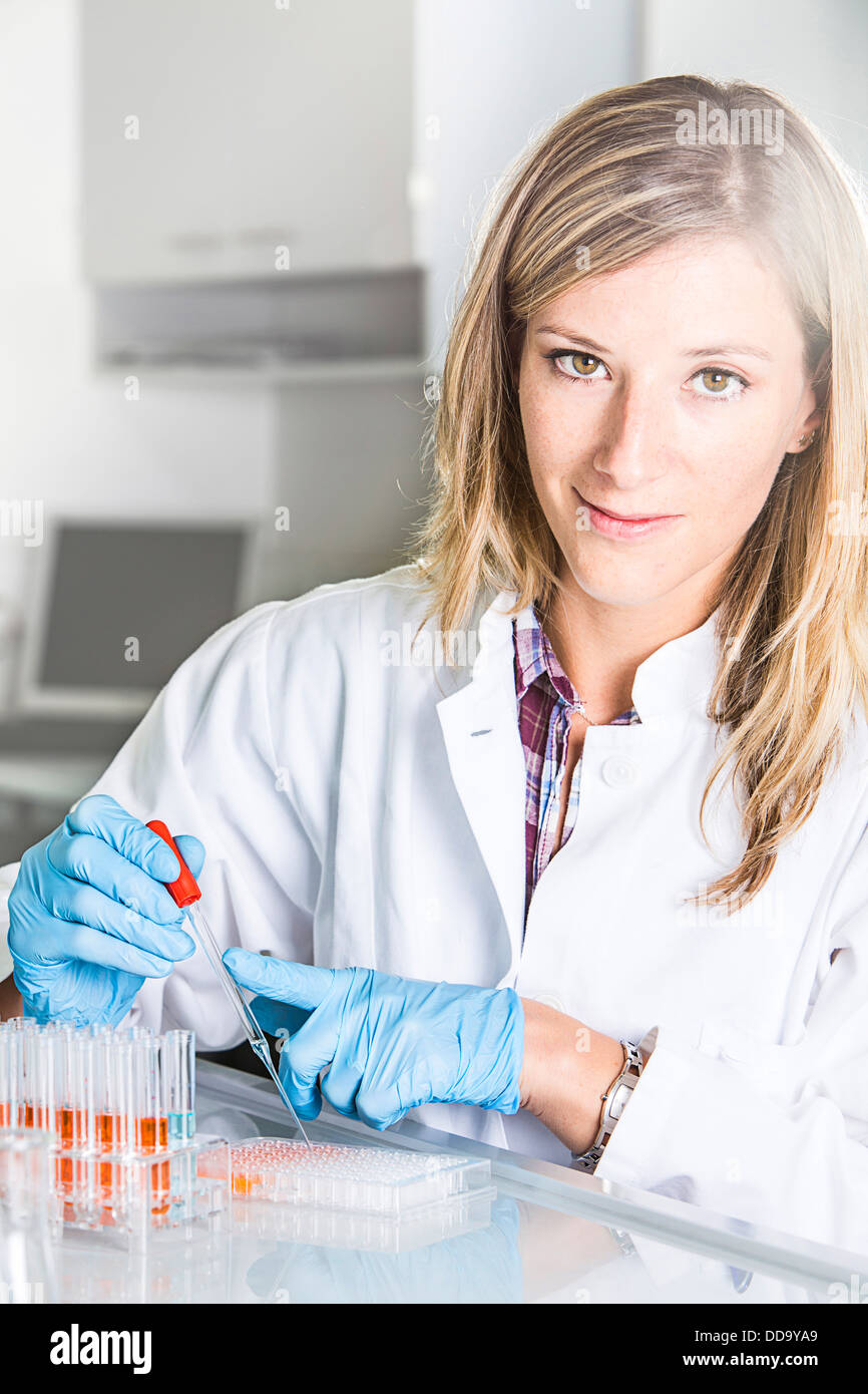 Portrait of female scientist at the laboratory with 96-wellplate and pipette - Stock Image