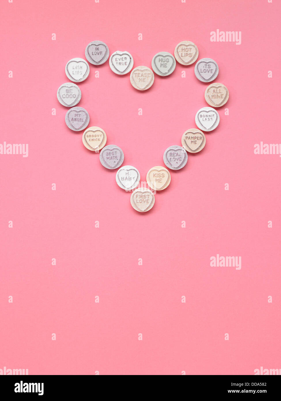 Love hearts positioned in the shape of a heart on a pink background - Stock Image