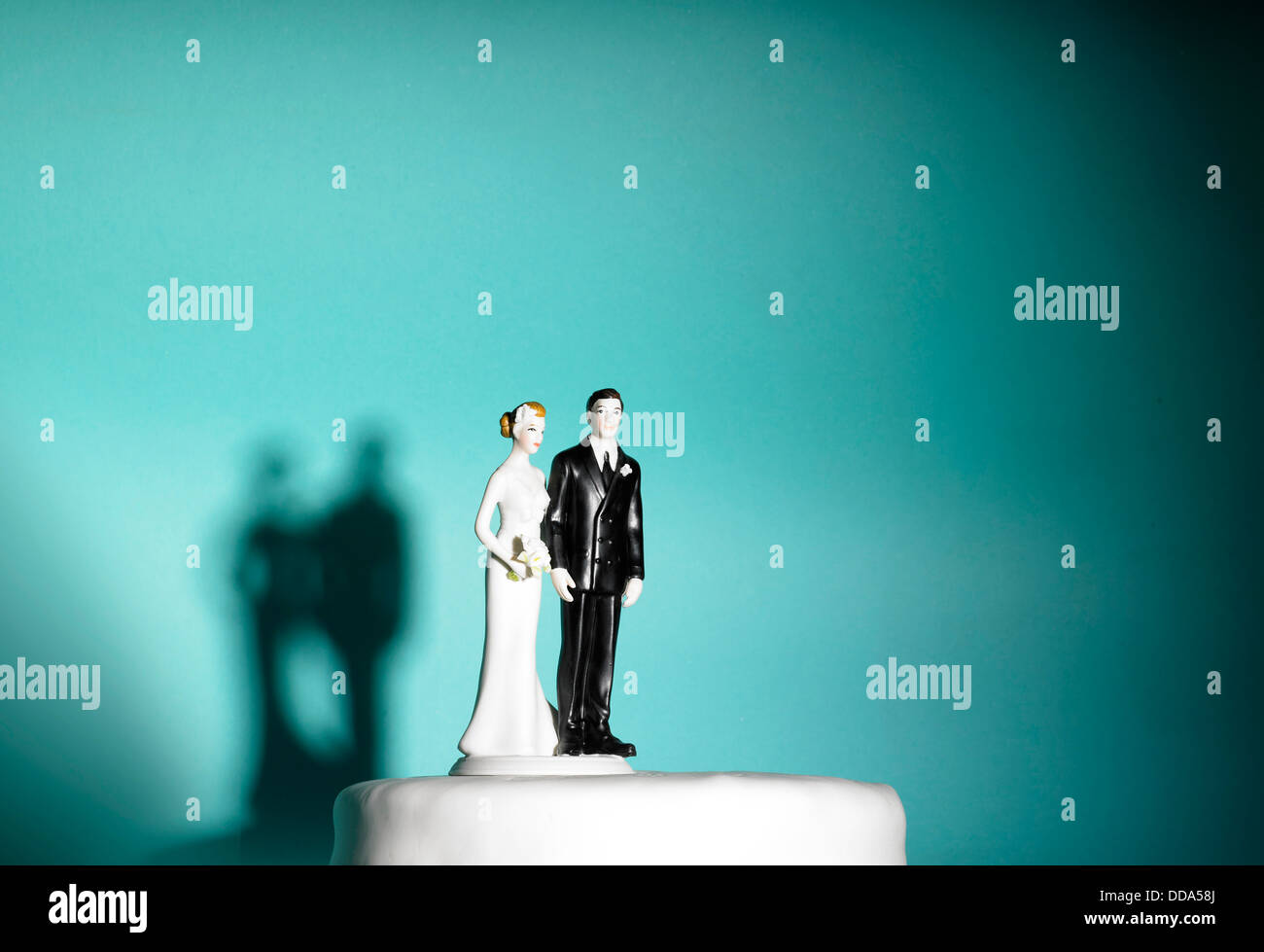 Bride and groom figures on a wedding cake on blue background - Stock Image