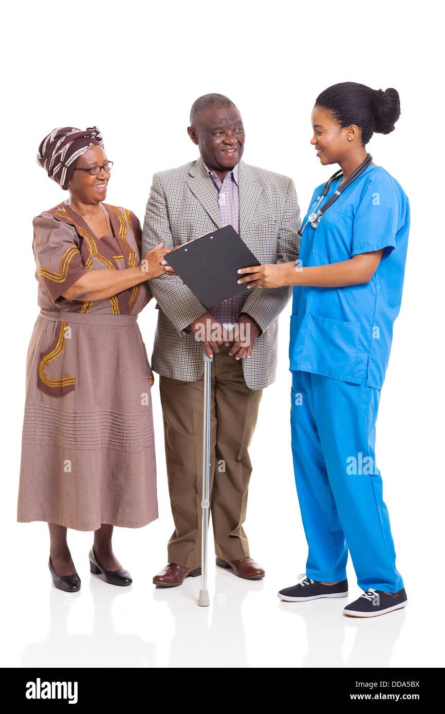 young female African nurse talking to senior couple isolated on white background - Stock Image