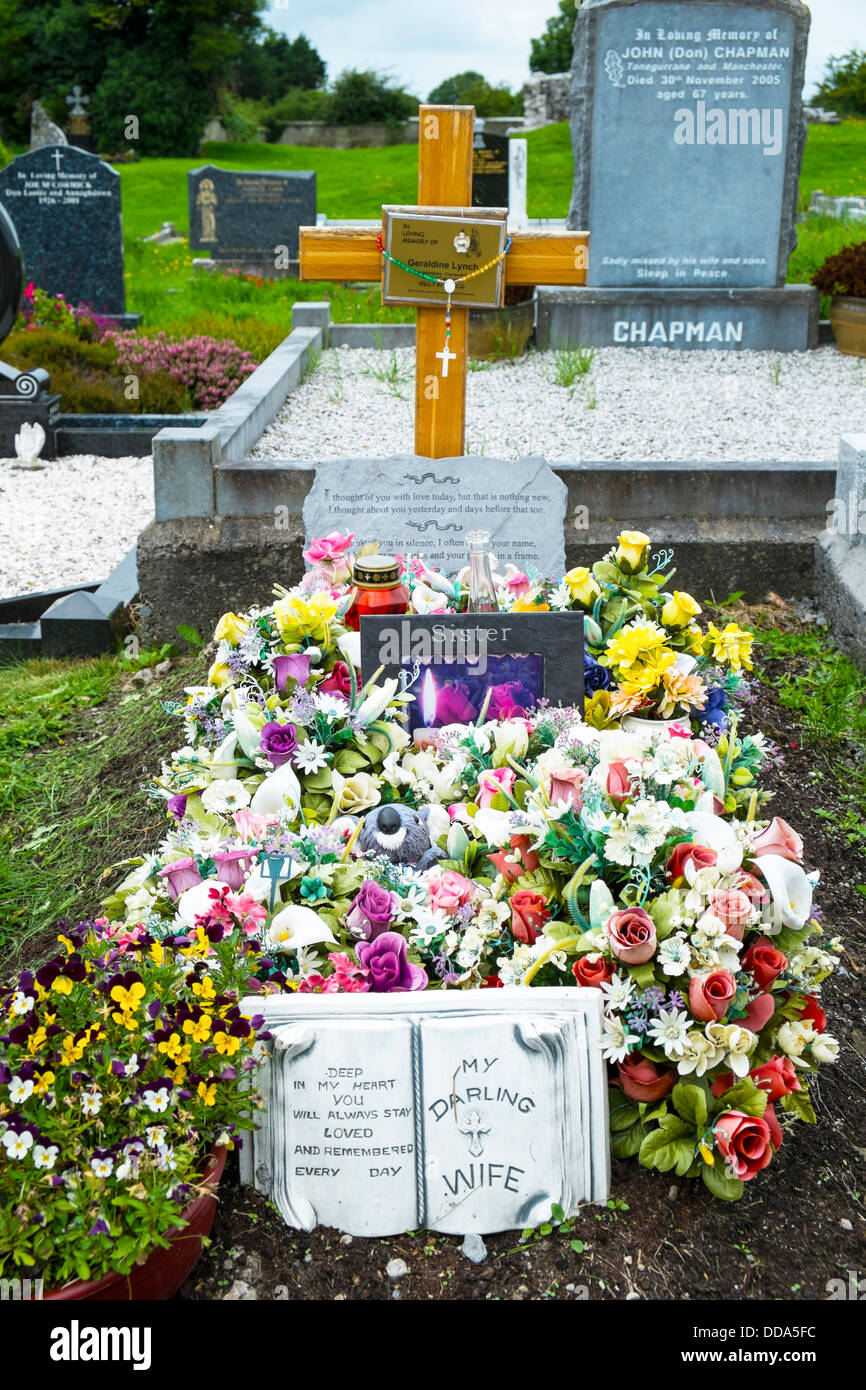 A grave in an Irish rural cemetery covered with plastic flowers - Stock Image