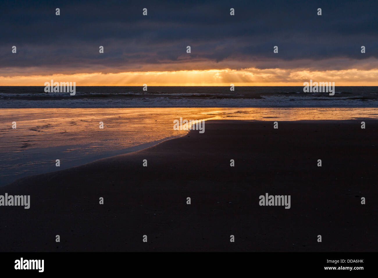 Sunset Over Water with Heavy Cloud and Rays - sunrise over Moeraki Beach, Otago New Zealand. - Stock Image