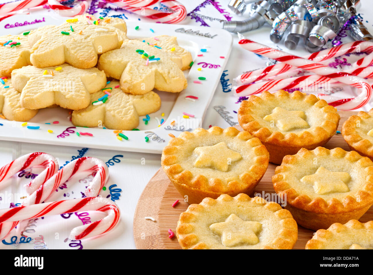 A buffet table set up for a celebration with Christmas fruit mince pies star shaped shortbread with sprinkles. & A buffet table set up for a celebration with Christmas fruit mince ...